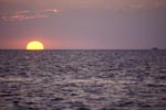 The sun sinks into the sea in front of Walker's Cay